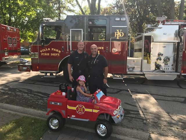 Fire Safety Personnel with a Girl in a Toy Fire Truck at the 2017 Block Party at South Euclid