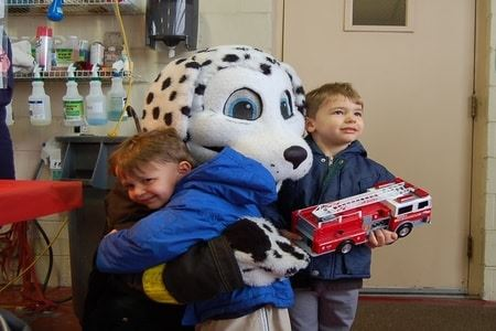 Kids Hugging a Person in a Sparky the Dog Costume