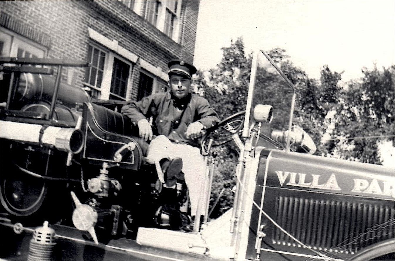 Villa Park Firefighter Bill Rutter sits in the driver's seat of a 1938 Pierce fire truck outside of Village Hall.